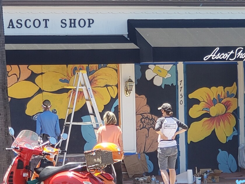 Volunteers paint a mural on the Ascot Shop on Girard Avenue.