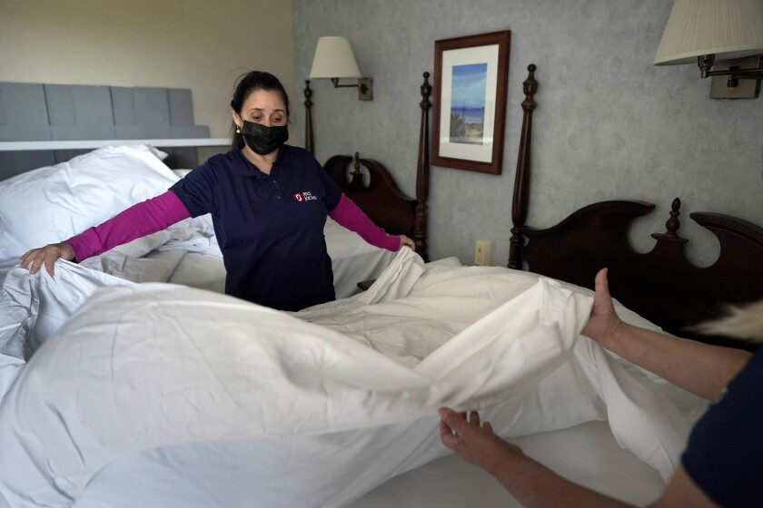 Miriam Mattos (izq) y Marilene Souto tienden una cama en el Red Jacket Resorts de Yarmouth