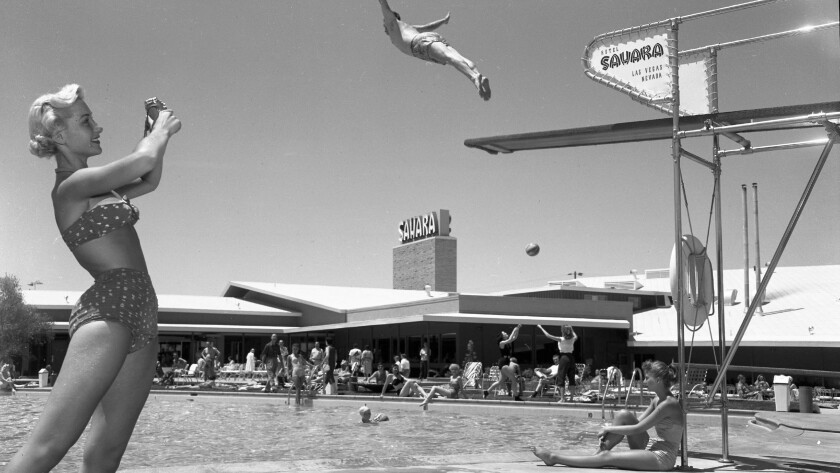 Several are gathered by the pool at the Sahara in 1953, including a woman in a two-piece bathing suit and a man in mid-leap off the diving board.