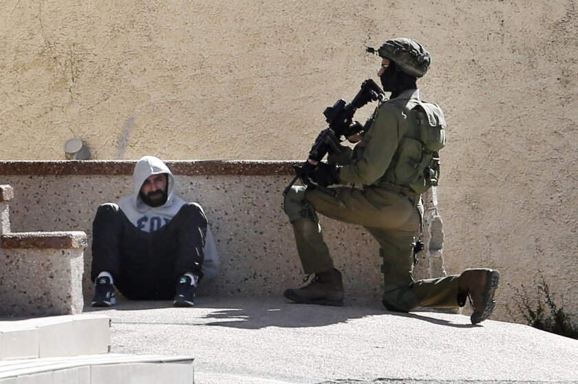 An Israeli soldier keeps guard by an arrested Palestinian man at the Amari Palestinian refugee camp, near the West Bank city of Ramallah during clashes with Palestinians that erupted after they entered the camp early in the morning, Monday, Feb. 15, 2016. (AP Photo/ Nasser Shiyoukhi).