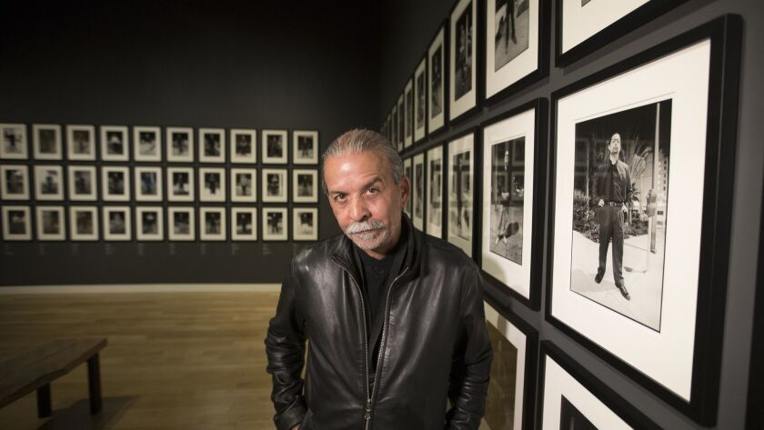 "Harry Gamboa Jr. with his portrait collection ""Chicano Male Unbonded."""