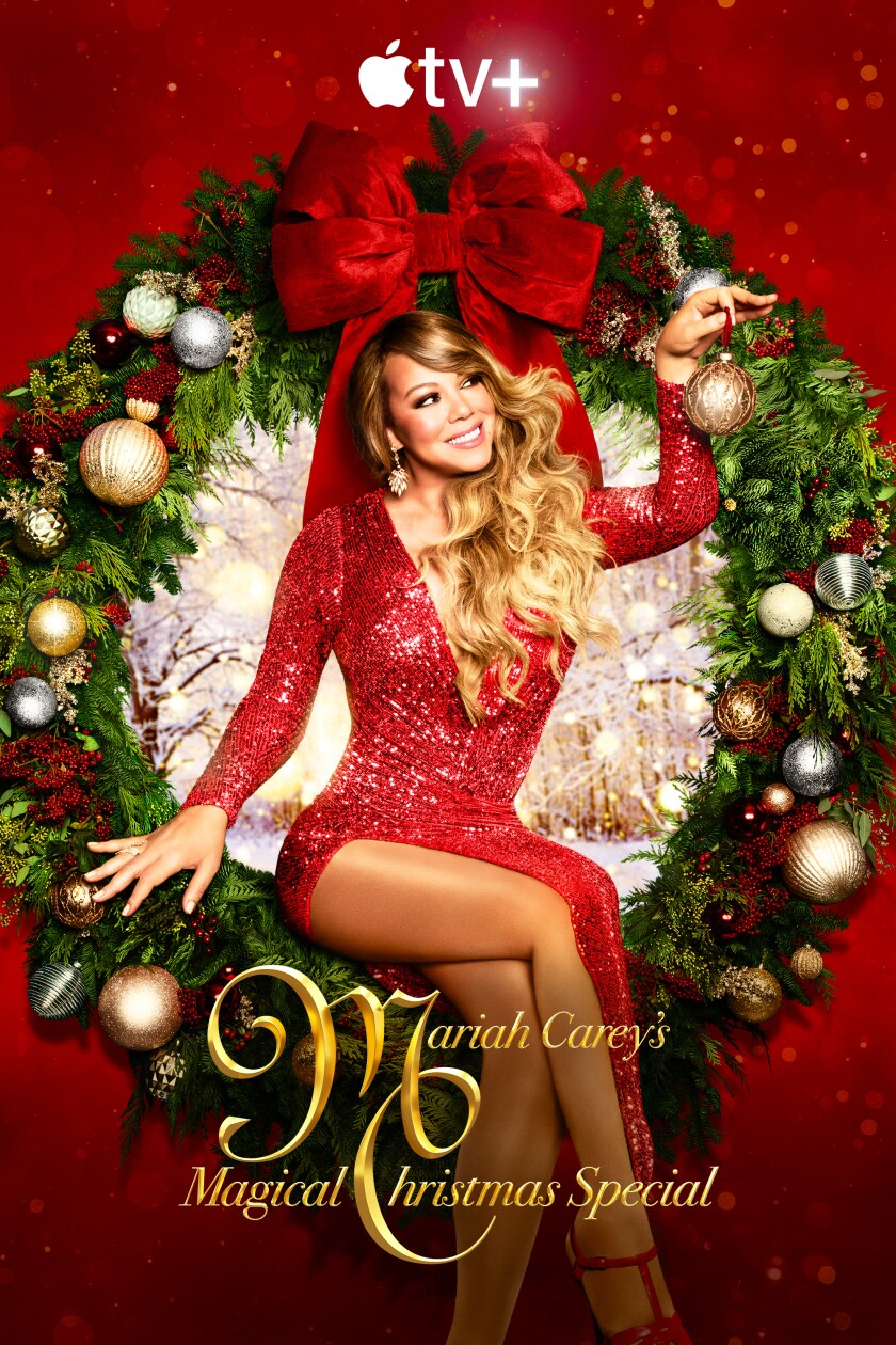 Mariah Carey in a red dress holding an ornament sitting in a Christmas wreath with a snowy woods scene behind her