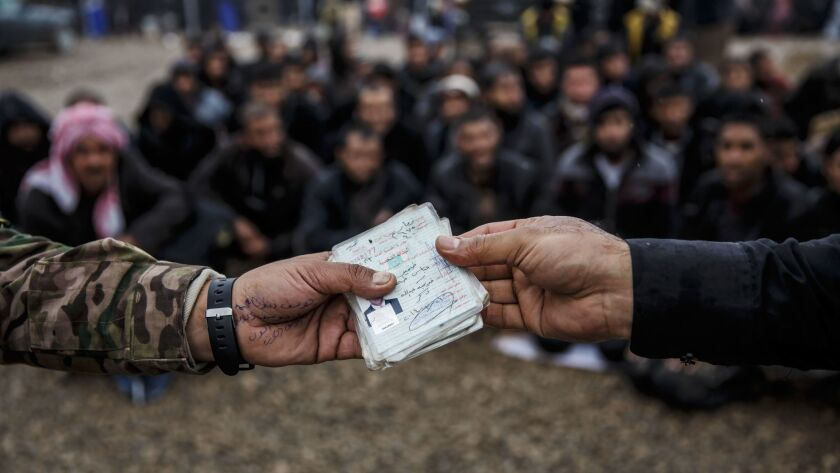 Identification papers of displaced people are checked against a database of Islamic State members at