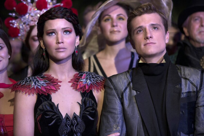 """This image released by Lionsgate shows Jennifer Lawrence as Katniss Everdeen, left, and Josh Hutcherson as Peeta Mellark in a scene from """"The Hunger Games: Catching Fire."""" The film releases Nov. 22, 2013. (AP Photo/Lionsgate, Murray Close)"""