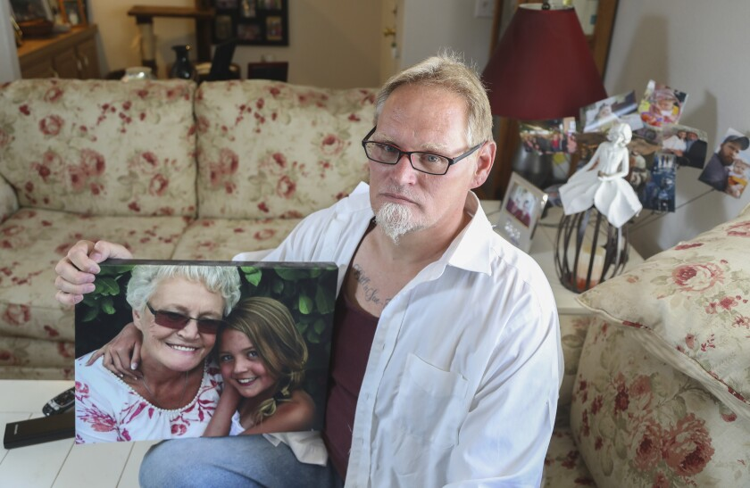 Chuck Beckner poses for a photo with a picture of his mother, Billy Sue Matchke, who died of COVID-19