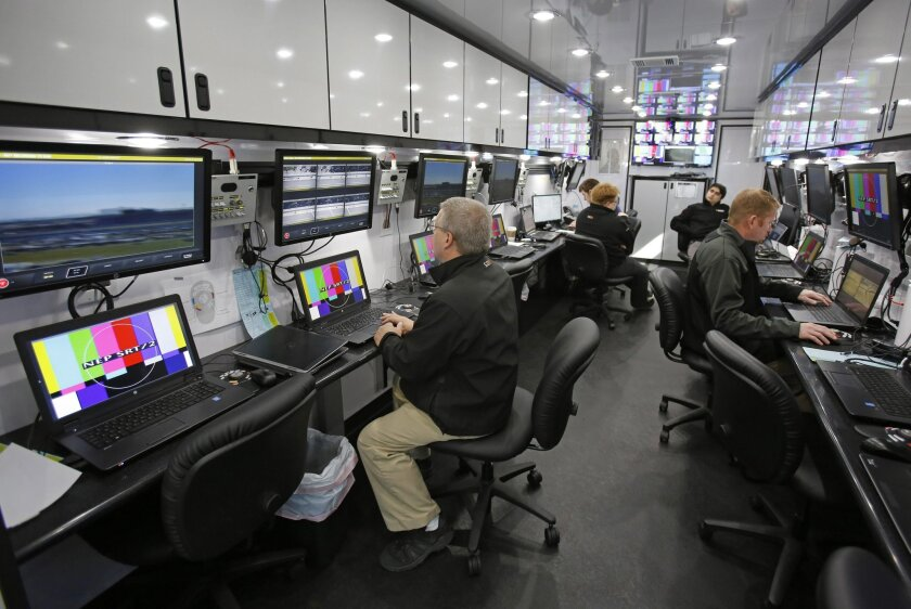 NASCAR officials check their video system to view pit stalls before a practice session for the Daytona 500 NASCAR Sprint Cup series auto race at Daytona International Speedway in Daytona Beach, Fla., Thursday, Feb. 19, 2015. The system is designed to help officials track rules violations in the pits during a race. (AP Photo/Terry Renna)