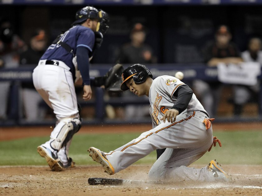 Baltimore Orioles' Jonathan Schoop (6) scores on an RBI single by Pedro Alvarez as Tampa Bay Rays catcher Bobby Wilson fields the wide throw in the ninth inning of a baseball game Tuesday, Sept. 6, 2016, in St. Petersburg, Fla. (AP Photo/Chris O'Meara)