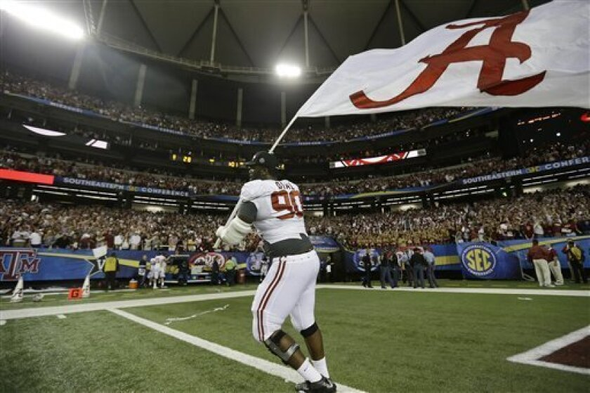 Alabama defensive lineman Quinton Dial (90) runs on the field with a Alabama flag after their 32-28 win in the Southeastern Conference championship NCAA college football game against Georgia, Saturday, Dec. 1, 2012, in Atlanta. (AP Photo/David Goldman)