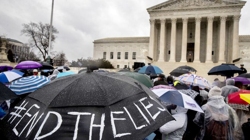 """Abortion-rights supporters hold an umbrella that reads """"#EndTheLies"""" outside the Supreme Court building on March 20 as the court hears arguments in a case concerning California's attempt to regulate antiabortion crisis pregnancy centers."""