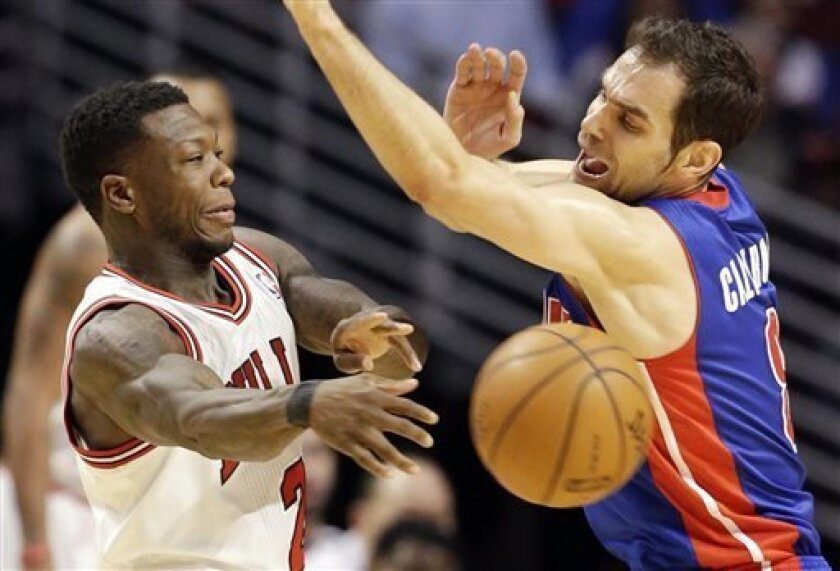 Chicago Bulls guard Nate Robinson, left, passes against Detroit Pistons guard Jose Calderon during the first half of an NBA basketball game in Chicago, Sunday, March 31, 2013. (AP Photo/Nam Y. Huh)