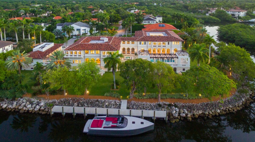 A waterfront mansion with a boat docked nearby