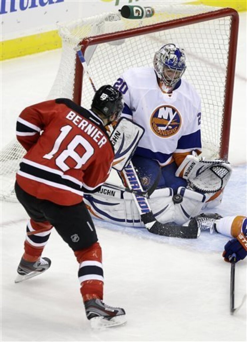 New York Islanders goalie Evgeni Nabokov (20) of Kazakhstan makes a save off his pads on a shot by New Jersey Devils' Steve Bernier (18) during the second period of an NHL hockey game Monday, April 1, 2013, in Newark, N.J. (AP Photo/Mel Evans)