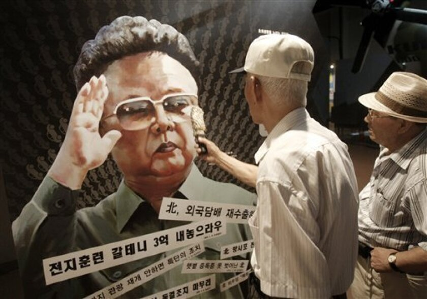 A visitor points with am umbrella at a poster of North Korean leader Kim Jong Il, painted by North Korean defector Sun Moo, at the Korea War Museum in Seoul, South Korea, Tuesday, Aug. 31, 2010. The Obama administration expanded sanctions against North Korea on Monday by freezing assets of individuals, companies and organizations allegedly linked to support for Pyongyang's nuclear program.(AP Photo/Ahn Young-joon)