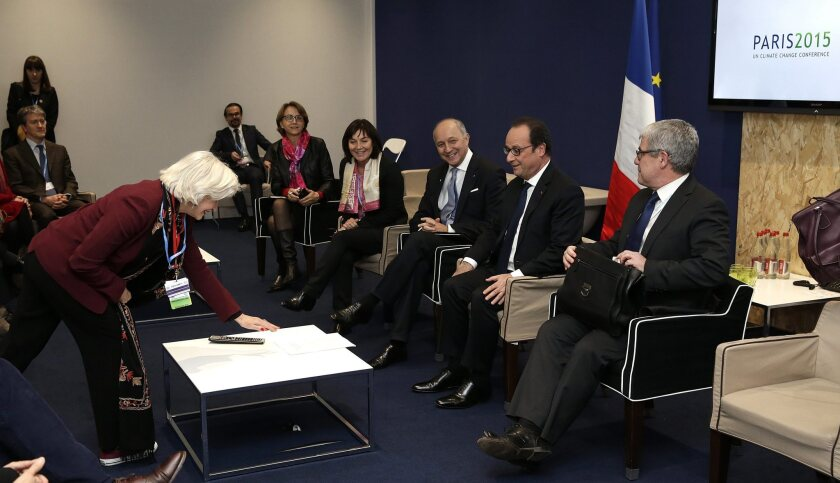 French President Francois Hollande, right, attends a meeting at the world climate change conference in Le Bourget, on the northern edge of Paris, on Saturday.