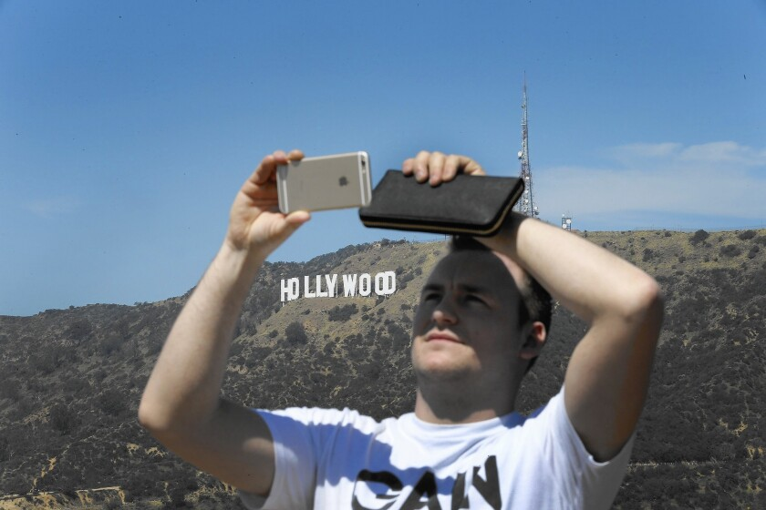 Robin Seimar of Sweden snaps a photo with the Hollywood sign in the background.