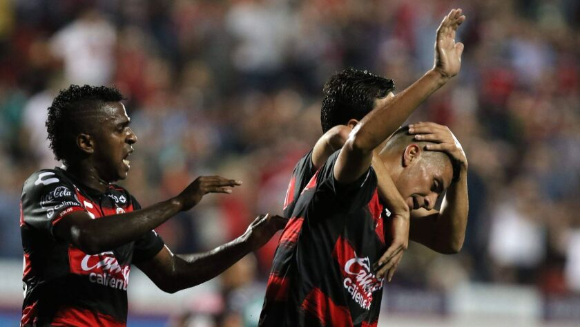 Tijuana's Diego Gonzalez (R) celebrates with teammates Miler Bolanos (L) and Erick Torres (right-back) after scoring, but Santos Laguna came back to tie the match.