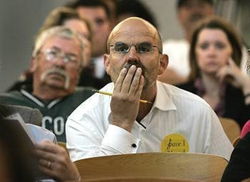 School district music teacher Dave Rouillard listens intently to public comment at a school board meeting where district trustees were considering possible elimination of music programs.