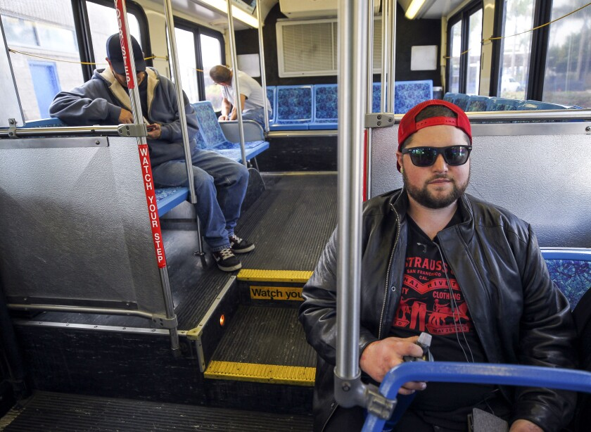 Anthony Egkert, right, who is on his way to work, sits on a NCTD Breeze bus just before it leaves from the Oceanside Transit Center on Saturday.