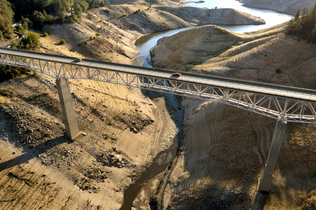 Vehicles cross a bridge across a nearly dry arm of a lake