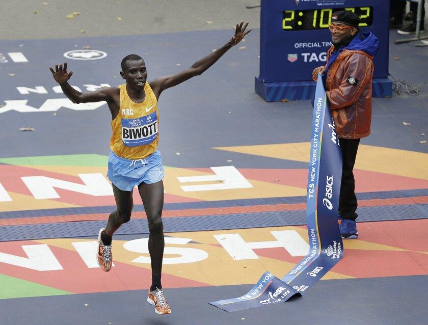 Stanley Biwott of Kenya, left, crosses the finish line first in the men's division at the 2015 New York City Marathon in New York, Sunday, Nov. 1, 2015.  (AP Photo/Seth Wenig)