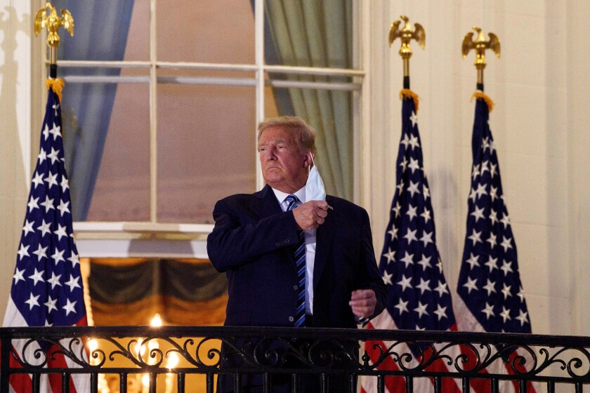 President Trump rips off his mask on a balcony at the White House after returning from the hospital