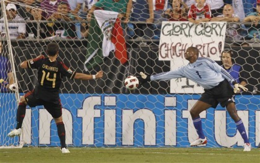 """Mexico's Javier """"Chicharito"""" Hernandez (14) heads in a goal past Cuba goalkeeper Odelin Molina (1) in the first half of a CONCACAF Gold Cup soccer match at Bank of America stadium in Charlotte, N.C., Thursday, June 9, 2011. (AP Photo/Bob Leverone)"""