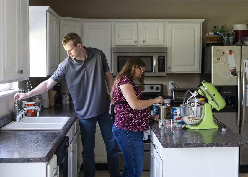 Rebecca Grimm makes homemade bread alongside her husband, Mark, at their home in Westfield, Ind., on Aug. 25. Grimm was pregnant with her second child in 2018 when she had a miscarriage. The couple were billed almost $6,000.