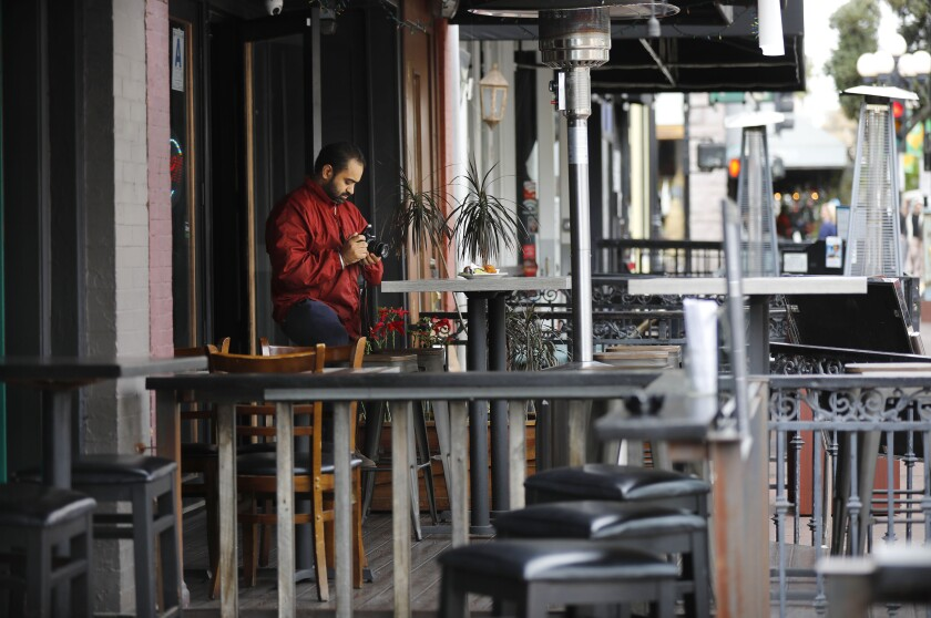 Surinder Singh, owner of Urban India restaurant in the Gaslamp Quarter, takes a photo of a dish to kill time with no customers in sight on March 16, 2020. The popular part of Downtown San Diego was all but empty even before quarantine rules were issued.