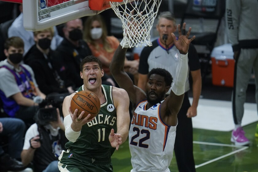 Milwaukee Bucks center Brook Lopez (11) shoots against Phoenix Suns' Deandre Ayton (22) during the first half of Game 3 of basketball's NBA Finals in Milwaukee, Sunday, July 11, 2021. (AP Photo/Paul Sancya)