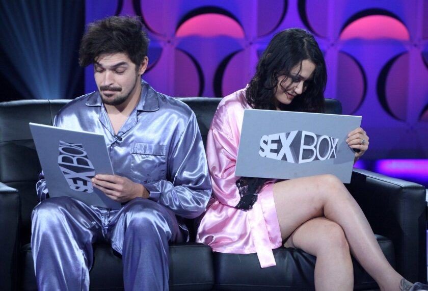 """This image released by WeTV shows contestants Elle, right, and Brandon during a taping of the new relationship therapy series """"Sex Box,"""" airing Friday at 10 p.m. EST. (AP Photo/WeTV)"""