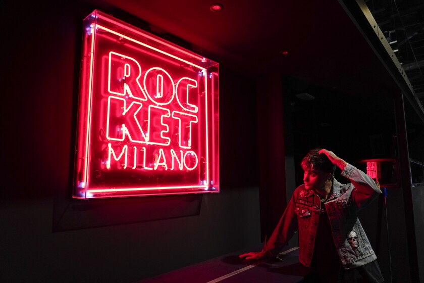 """Italian Dj Richey V, real name Francesco Orcese, looks at a neon sign inside Rocket Club, in Milan, Saturday, Sept. 25, 2021. Richey V, who created """"Void"""" which briefly became the unmissable appointment for a Thursday night in Milan, and is perhaps the most famous techno club in the region, said the early days of lockdown was like a psychological holiday from his busy calendar. With Italy's vaccination campaign now advanced, the government has finally given the green light for nightclubs to reopen this weekend. It's been a long wait. They are recommending that venues can open at 50% capacity indoors, and 70% in the open air. (AP Photo/Alberto Pezzali)"""