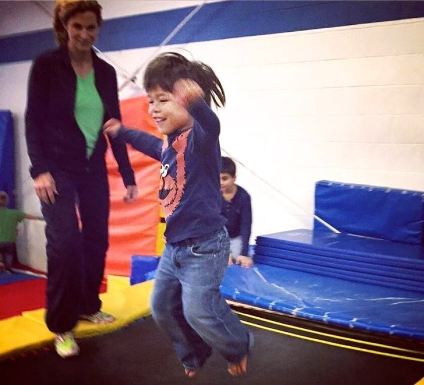 A youngster enjoys the freedom of movement at the first YMCA — San Diego Autism Society event held recently at the Ecke Y Gymnastics Center. Courtesy photo