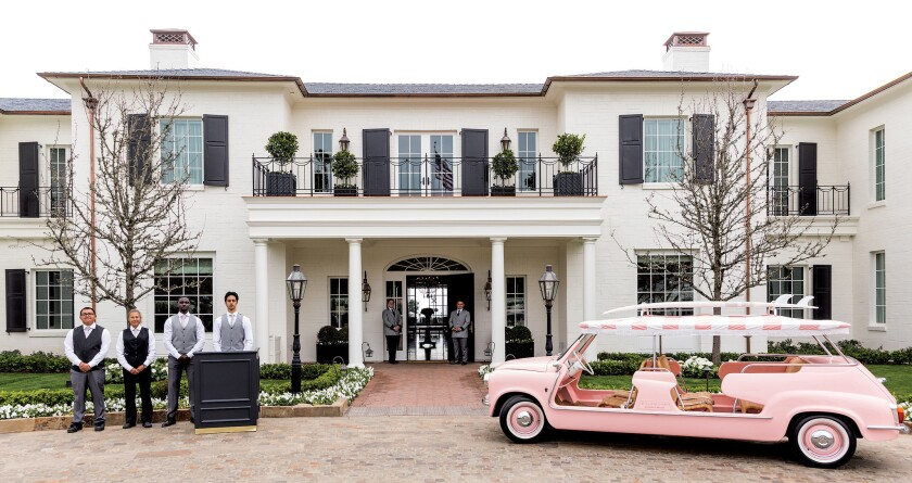 Exterior of front at the Rosewood Miramar Beach hotel in Montecito, CA with pink car and staff