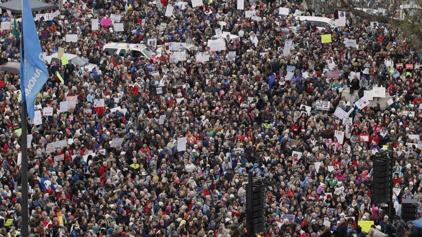 A crowd listens to speakers on a stage, lower right, during a teacher rally to protest low student f