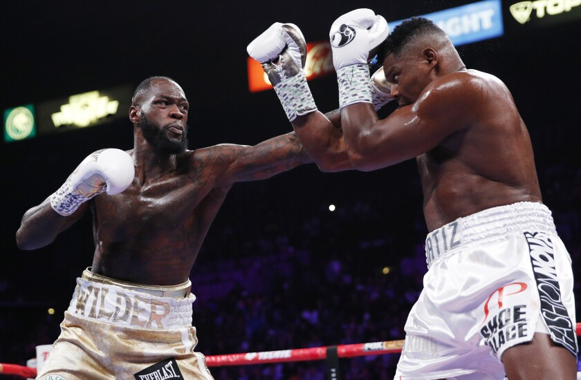 Deontay Wilder, left, throws a left at Luis Ortiz during the WBC heavyweight title boxing match on Saturday in Las Vegas.