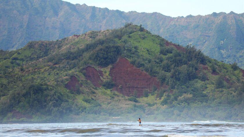 A man paddles one morning in Hanalei Bay, Kauai, before the devastating mid-April rains.