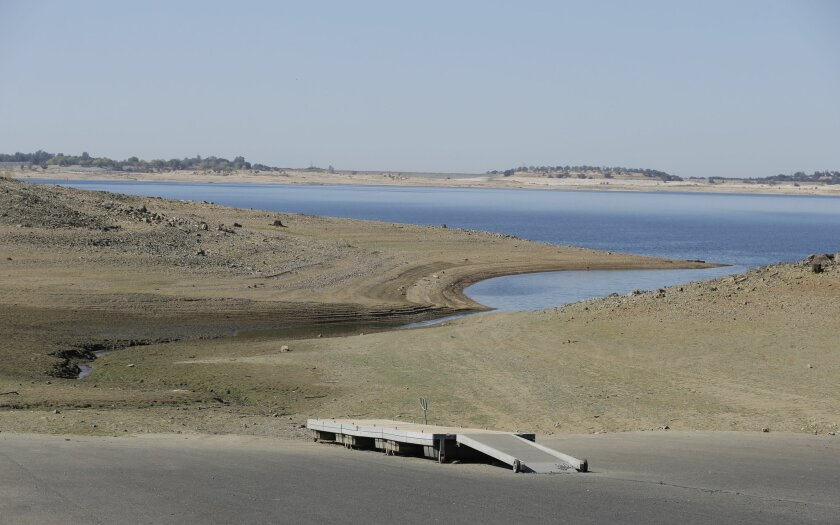 In this photo taken Oct. 6, 2014, a dock sits high and dry at the end of a boat ramp yards away from the edge of Folsom Lake near Folsom, Calif. The California Department of Water Resources reported Tuesday, Oct. 7, 2014, the largest monthly decline in water use this year as the severity of Califor