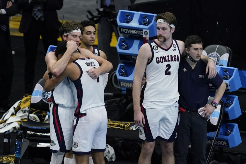 Gonzaga forward Corey Kispert (24) hugs Jalen Suggs (1) as Gonzaga forward Drew Timme (2) looks on at the end of the championship game against Baylor in the men's Final Four NCAA college basketball tournament, Monday, April 5, 2021, at Lucas Oil Stadium in Indianapolis. Baylor won 86-70. (AP Photo/Darron Cummings)