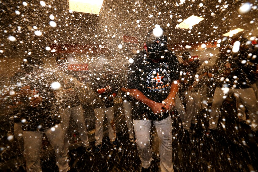 The Houston Astros celebrate in the locker room after clinching the American League pennant with a 6-4 win over the New York Yankees on Oct. 19.