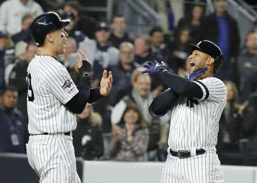 New York Yankees' batter Aaron Hicks, right, celebrates with teammate Aaron Judge after hitting a three-run home run in the bottom of the first inning against the Houston Astros in Game 5 of the ALCS on Friday in New York.