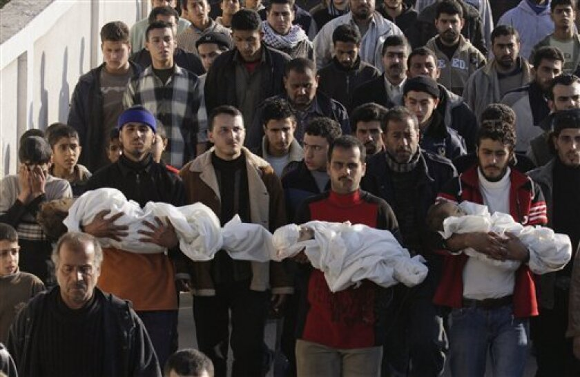 In this Monday, Jan. 5, 2009 file photo, Palestinians carry the bodies of three toddlers Ahmed, Mohamed, and Issa Samouni, who according to Palestinian medical sources were killed in an Israeli strike, during their funeral in Gaza City. At least 169 children and teens, ages 17 and under, have been