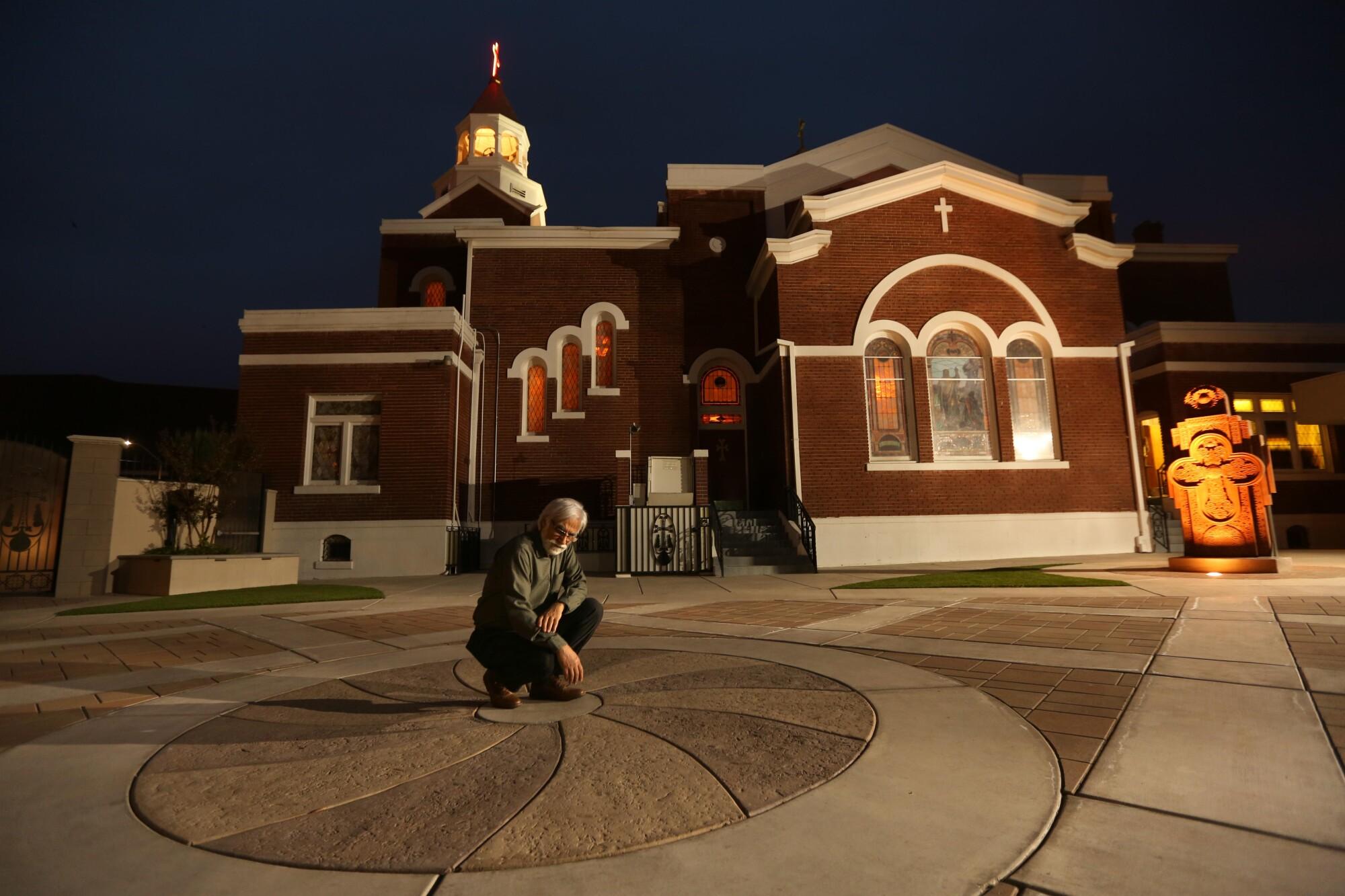 Varoujan Der Simonian kneels in the center of a concrete design outside a church