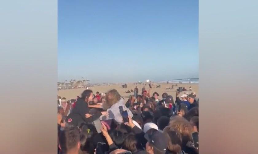 A crowd assembles in Huntington Beach on the sand near the ocean.