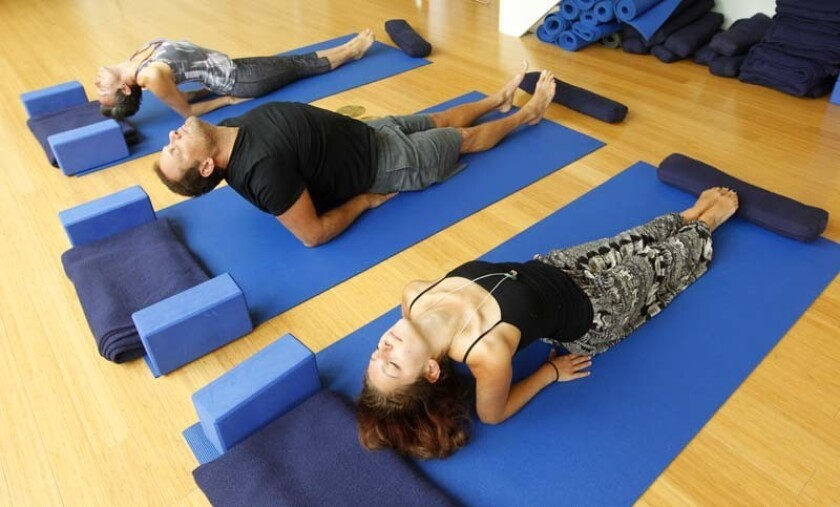 Emily Ruth, top, Stephen Beck, and Alisa Tiburzi do yoga at the Yoga Loft, which Beck owns in San Diego. The Yoga Loft will be on the new fitness app Lymber, which offers fitness classes at a number of health and fitness locations with no membership fee a