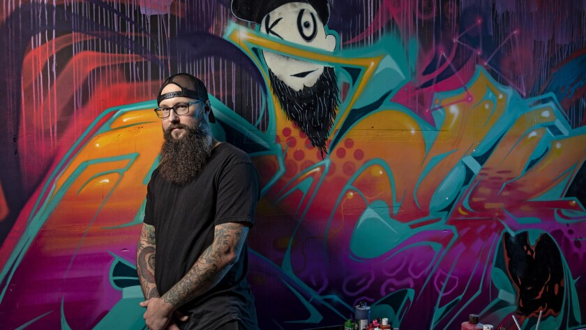 """LOS ANGELES, CA - February 08, 2019 - Troy Cole AKA """"Kickasso"""" posing in front of a mural by artist"""