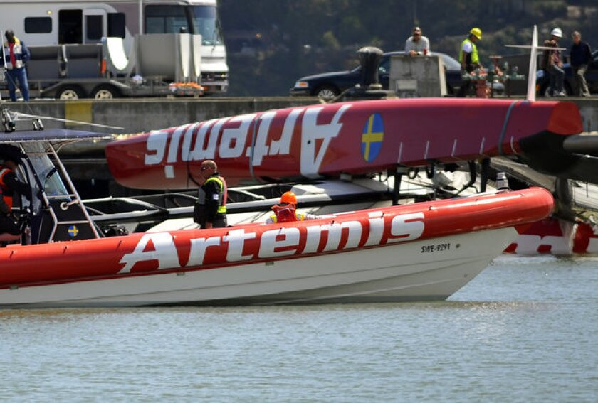 Artemis crew members continue operations to remove their damaged boat from San Francisco Bay off Treasure Island on Thursday.