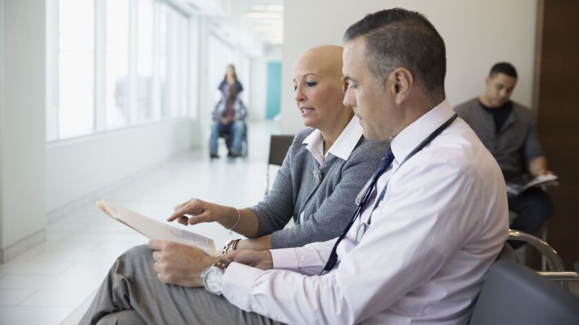 Male doctor discussing medical chart with bald female cancer patient in waiting room