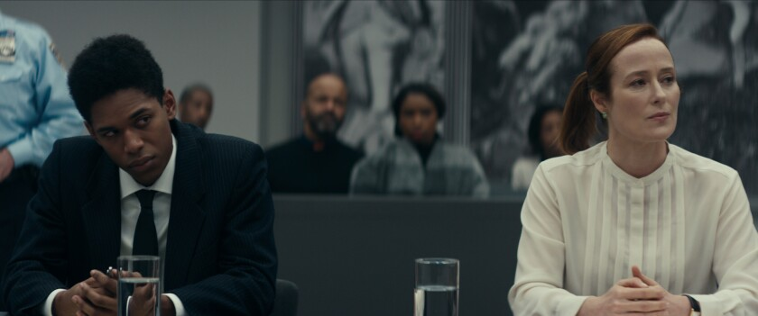 Kelvin Harrison Jr., in a suit, and Jennifer Ehle sit in court; Jeffrey Walker and Jennifer Hudson are in the background.