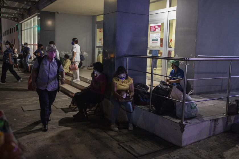 People sit outside a hospital