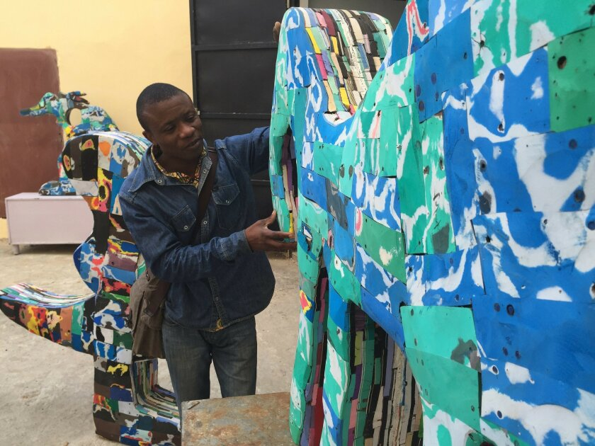 In this photo taken Tuesday May. 10, 2016, Togo's artist Komla Eza, shows his work as part of the Dak'Art OFF, during Dakar Biennele, Africa's largest contemporary art festiva, in Dakar, Senegal. His sculptures are made from recycled and compressed flip flops and shaped into animal-like forms to fo